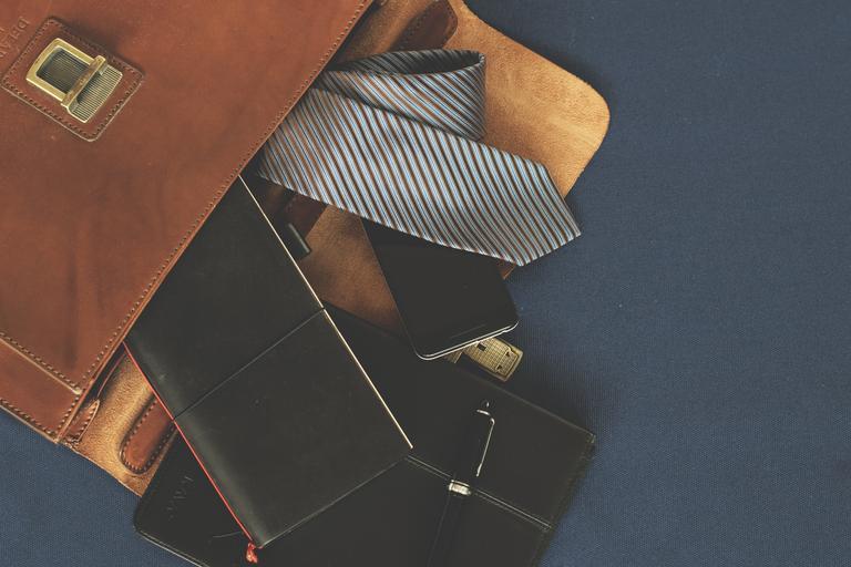 Otvorená kožená aktovka, kravata, mobil