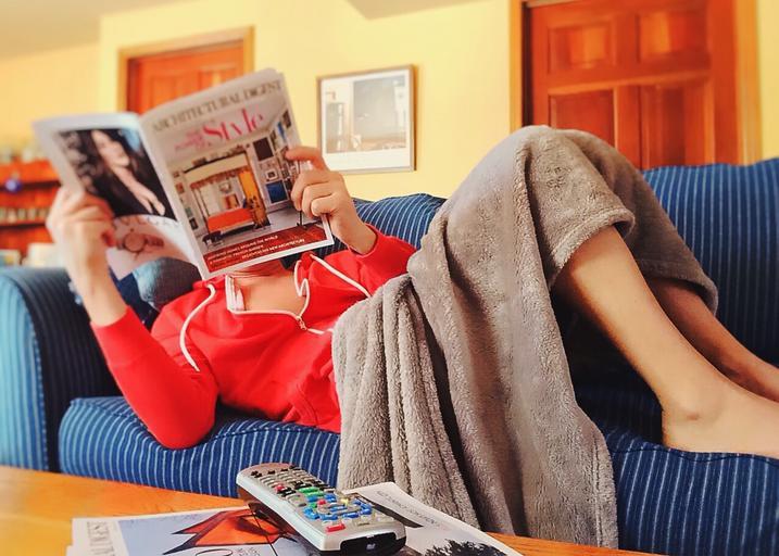 Žena relaxuje na gauči, číta časopis