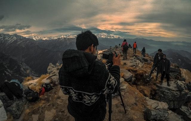 Muž v pletenom svetri, fotografuje ľudí na vrchole hory