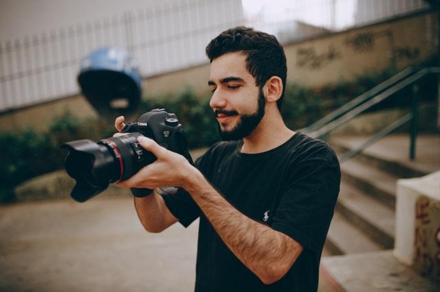 Chlapec v čiernom tričku stojí pri schodoch a fotografuje s veľkým fotoaparátom