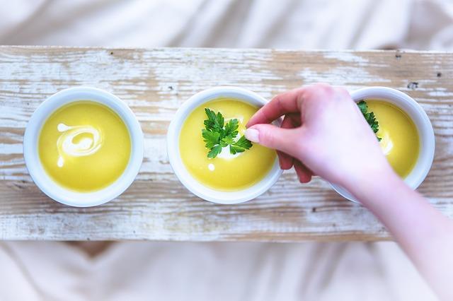 Tri biele misky na drevenej doske s krémovými oranžovými polievkami.jpg