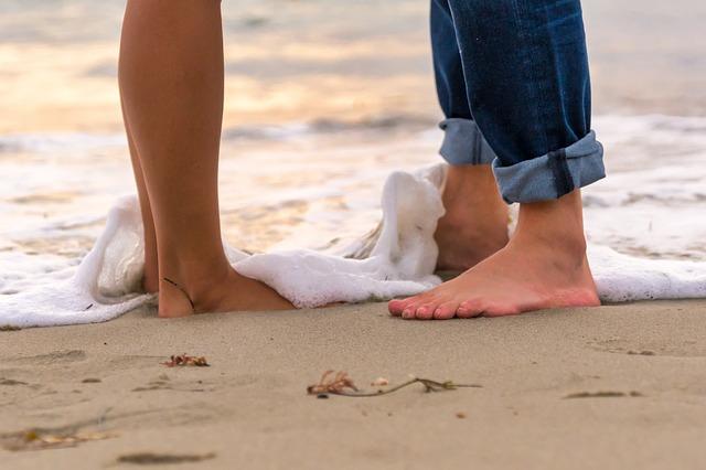 Muž a žena stoja s bosými nohami v prílive na pláži.jpg