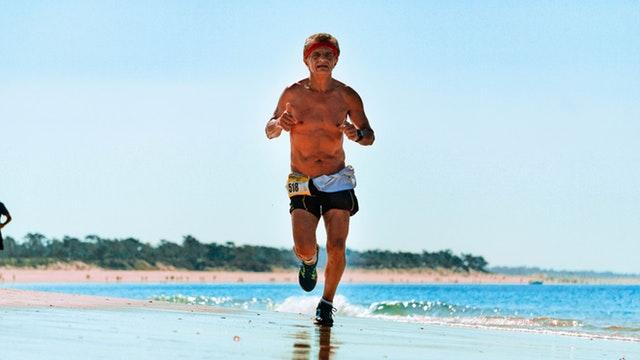 Starší muž v šortkách beží po pláži.jpg