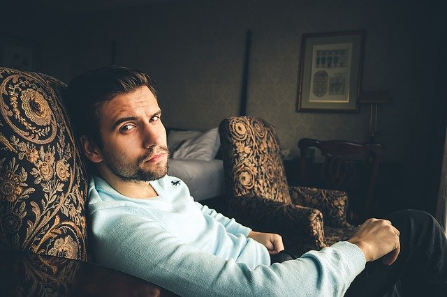 Mladý muž v bunde sedí na kresle v obývačke.jpg