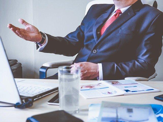 Šéf v modrom obleku sedí za stolom v kancelárii.jpg