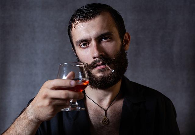 Muž s bradou drží v ruke pohárik s alkoholom.jpg
