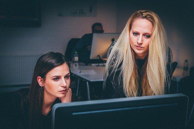 Dve ženy sedia pri počítači